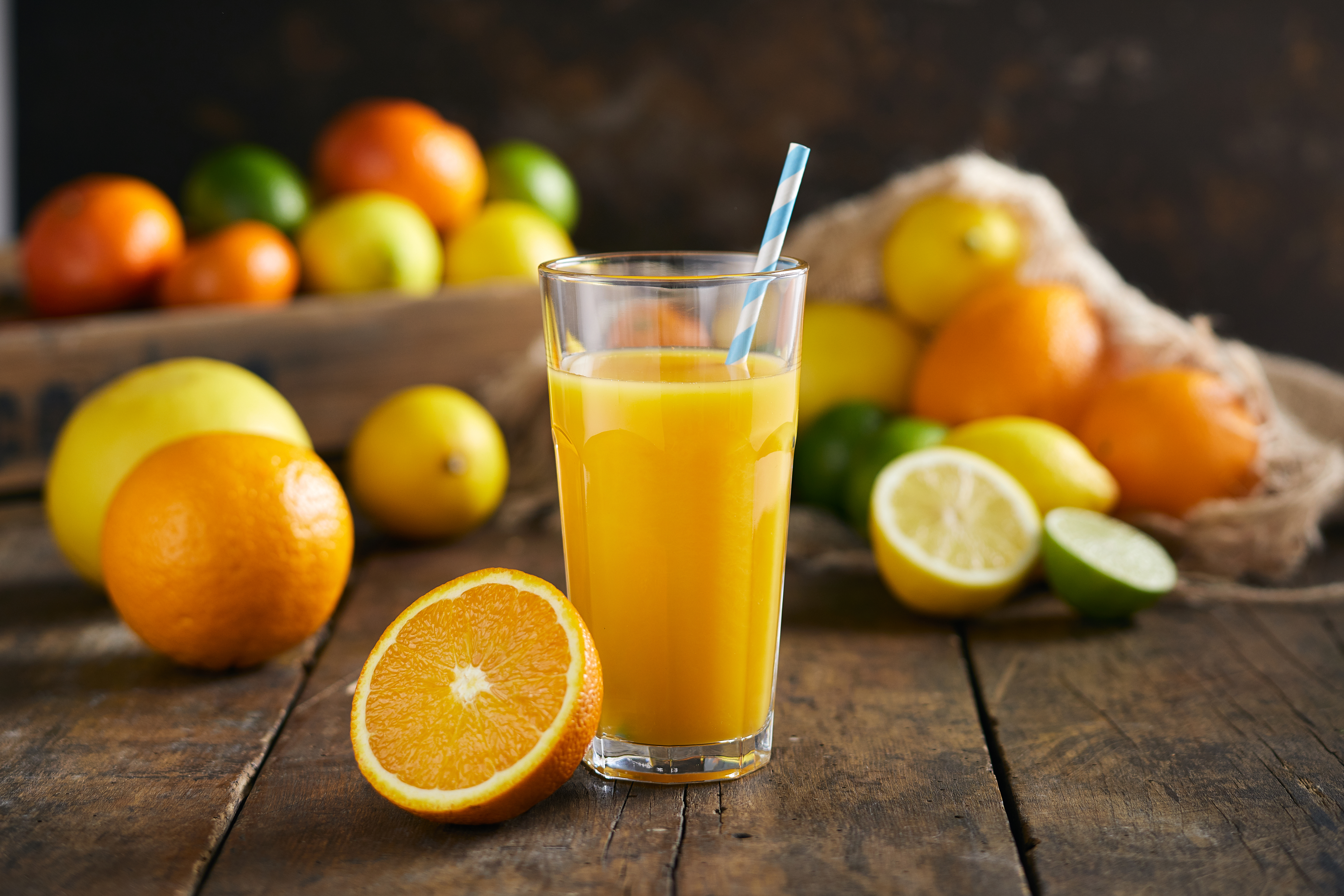 Glass full of orange juice with a paper straw on a dark wooden background. Halved orange is infront of a glass and mixed citruses are in the background.