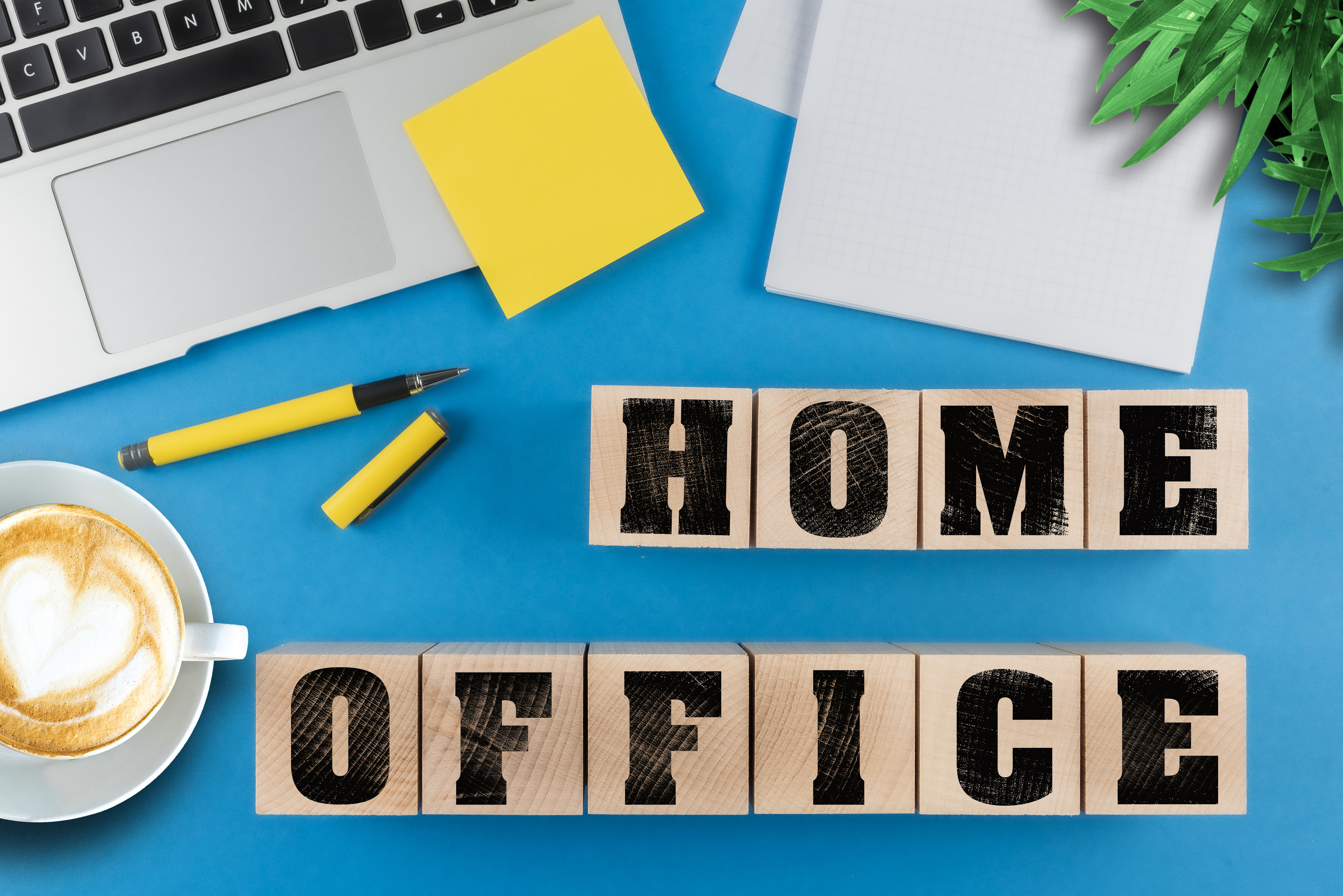 working from home concept, text HOME OFFICE on wood cubes besides laptop computer and notepad on desk