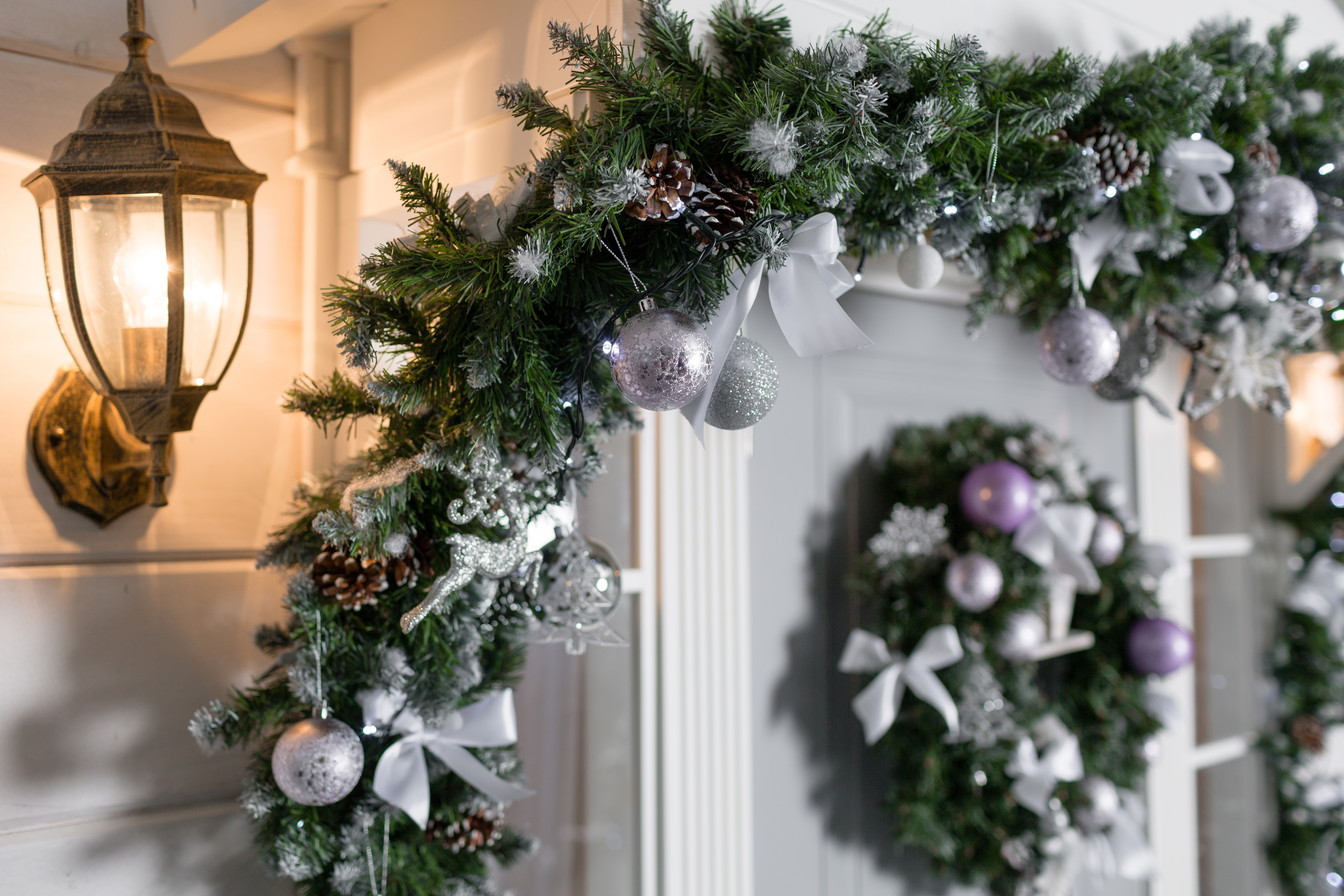 house entrance decorated for holidays. Christmas decoration. garland of fir tree branches and lights on the railing.