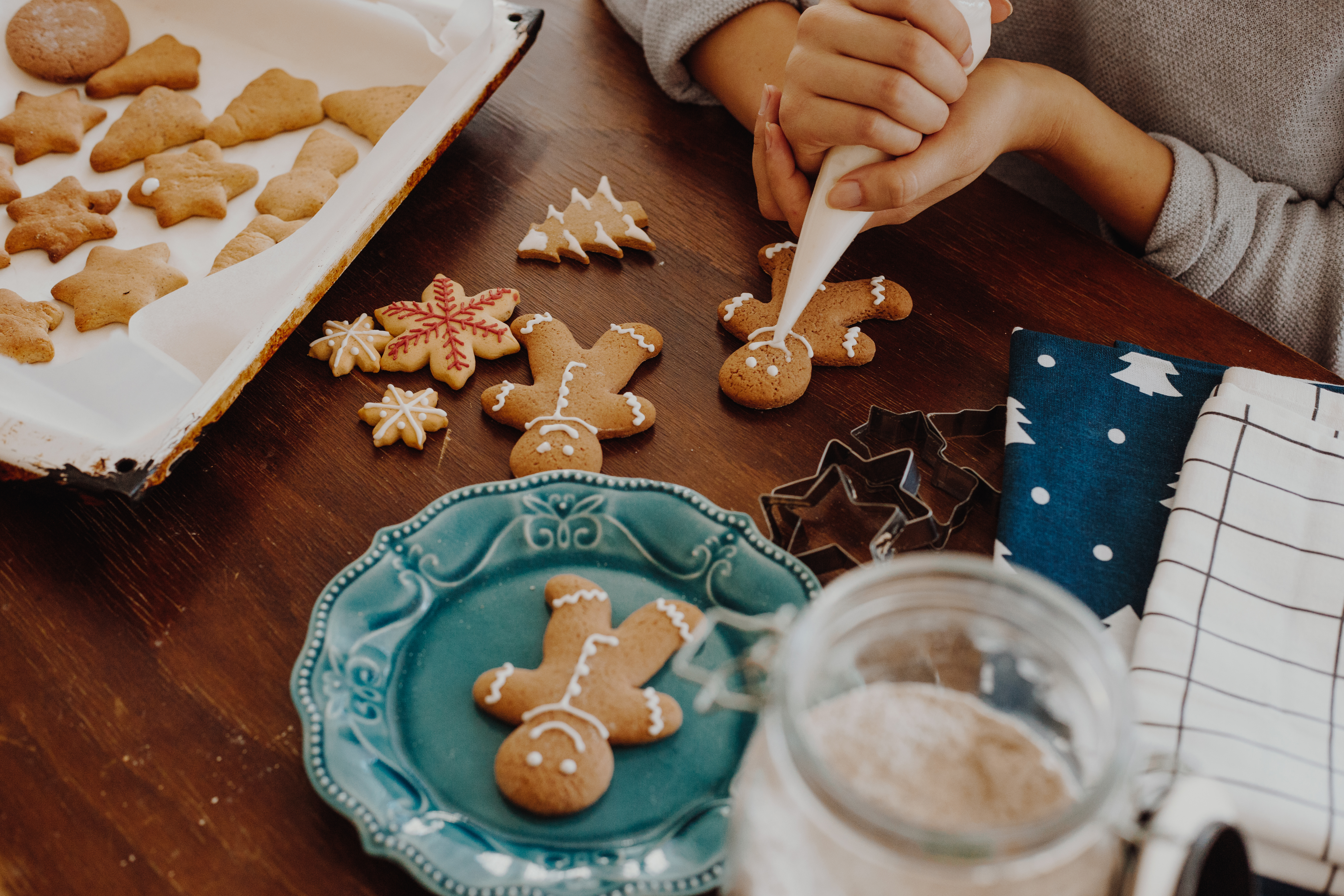 Women decorating gingerbread cookies, Christmas is near and she prepare for holidays.