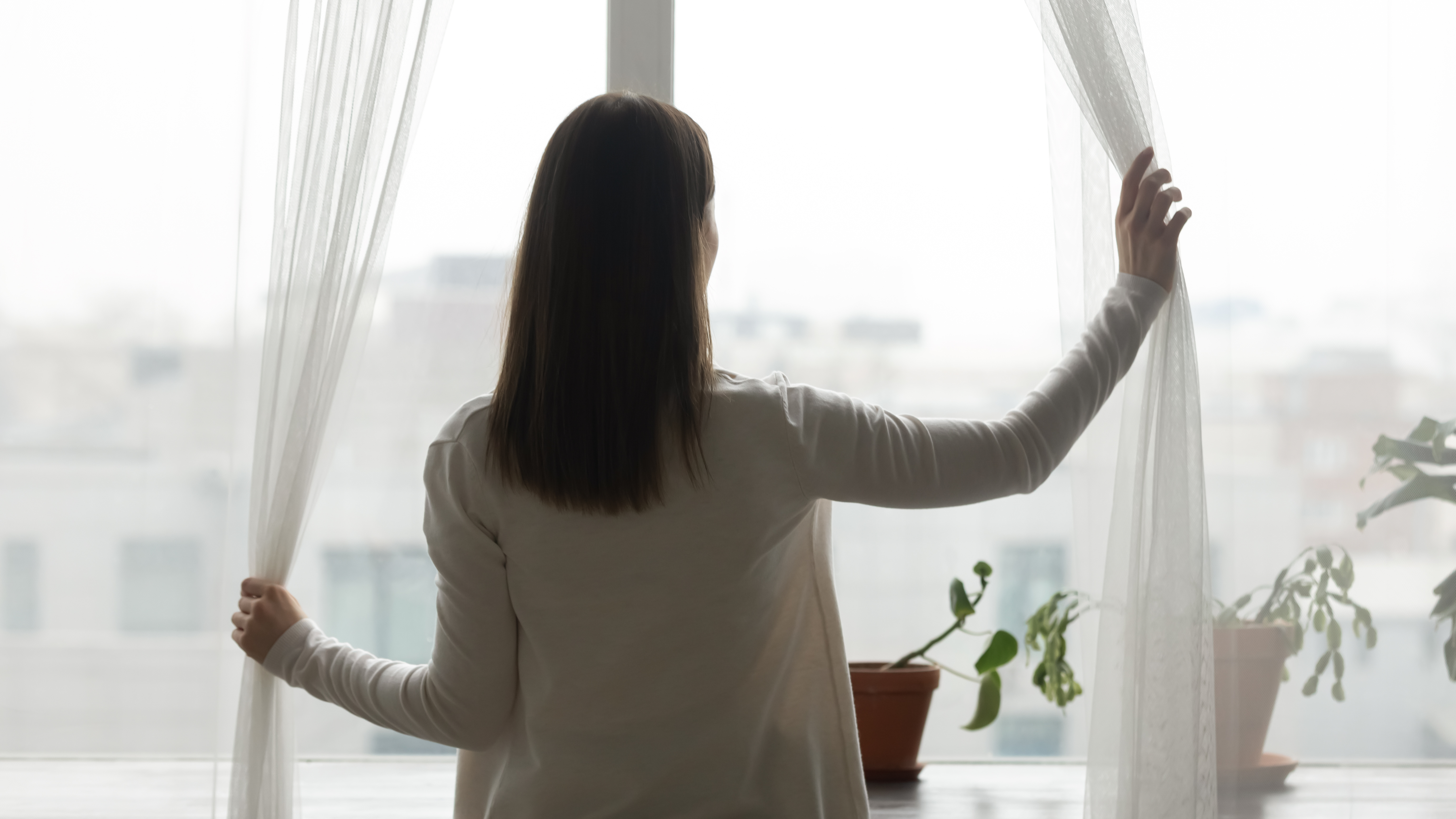 Rear back view young happy woman opening curtains, welcoming new day alone at home. Millennial dreamy brunette girl looking out of window, admiring panoramic city view or watching weather outside.