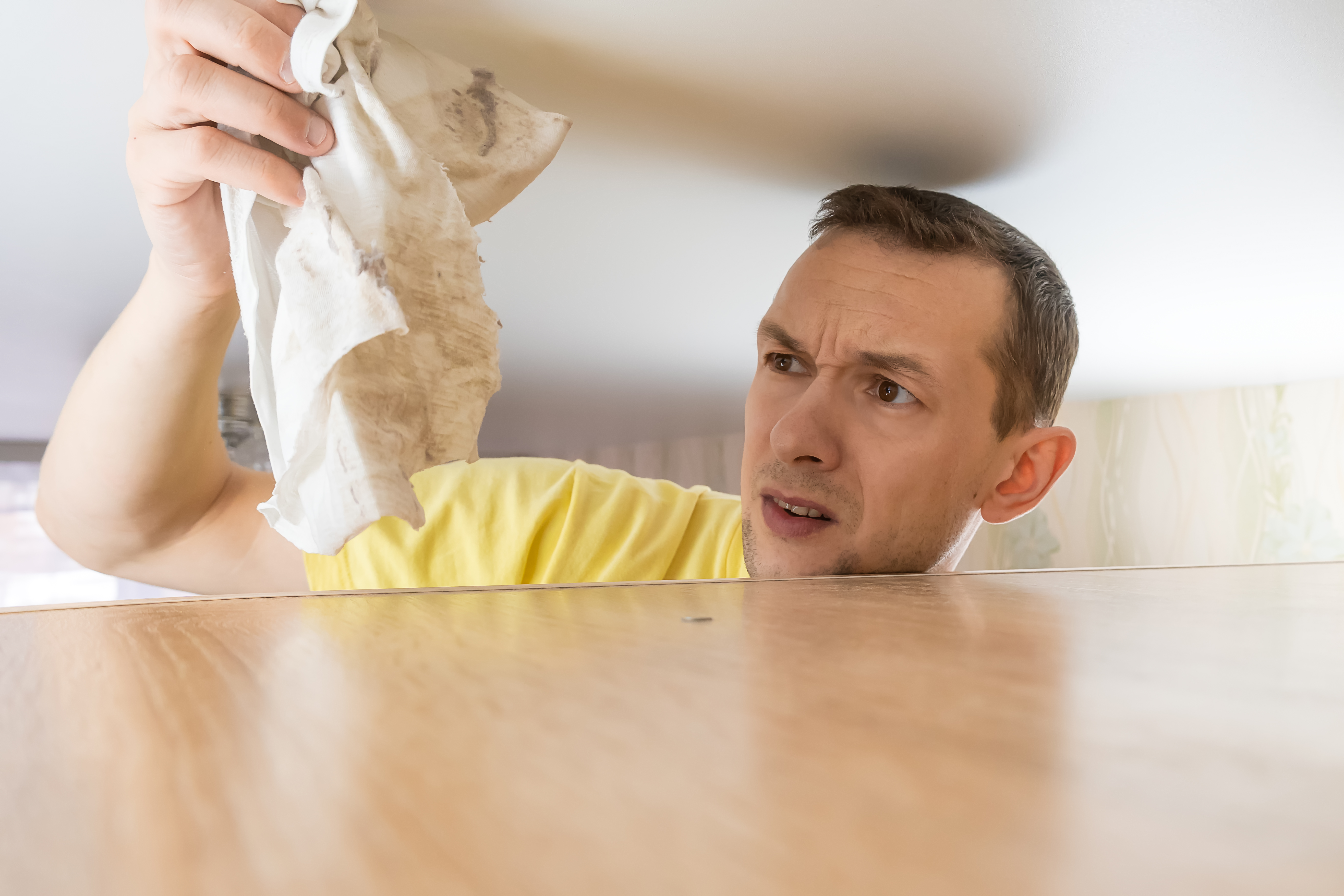 Concept of cleaning the house. a man wipes dust from a tall cabinet in his house. he goes up to the ceiling and looks at the dirty dust rag.