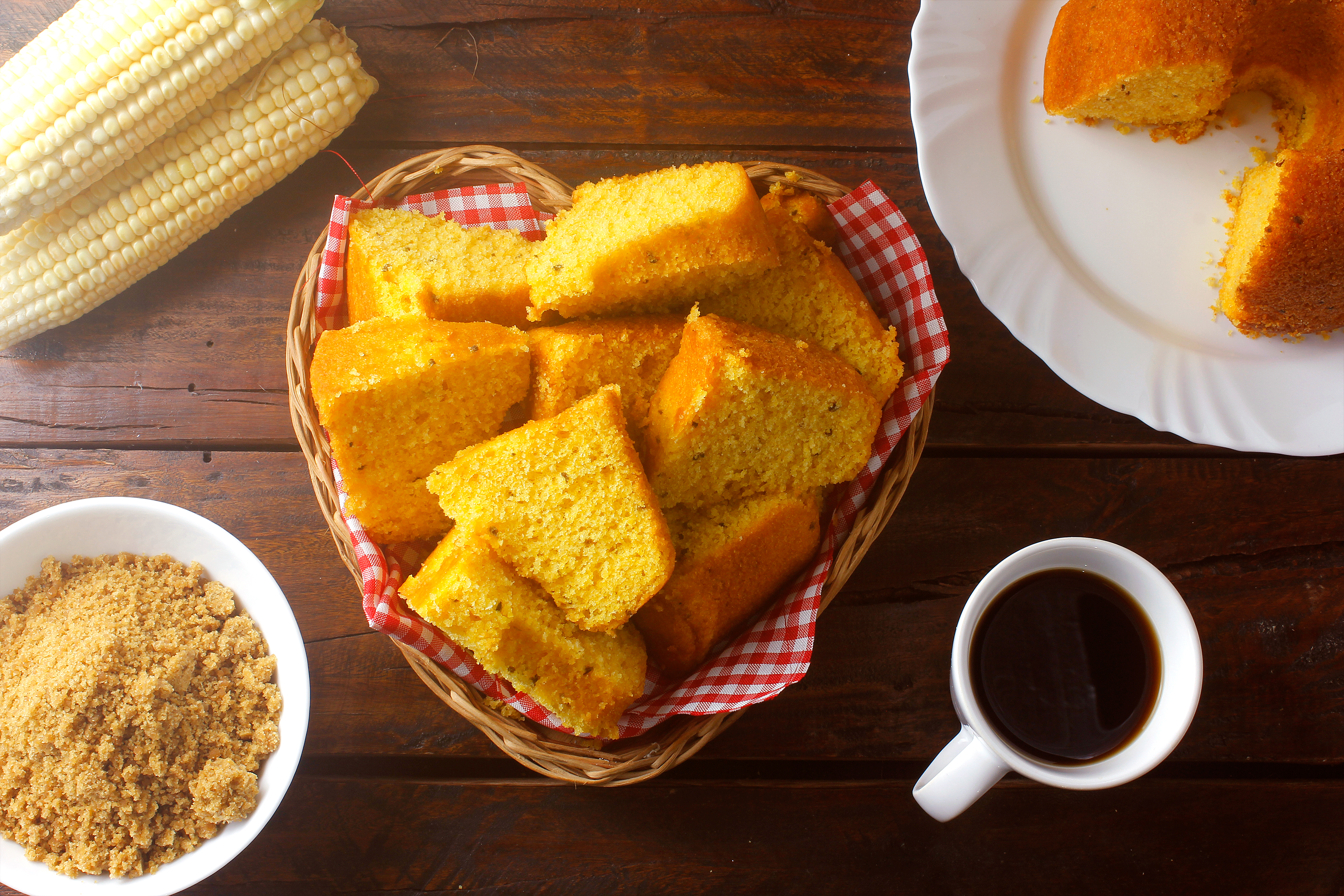 corn cake sliced in basket on rustic wooden table for breakfast. Typical Brazilian food. Top view