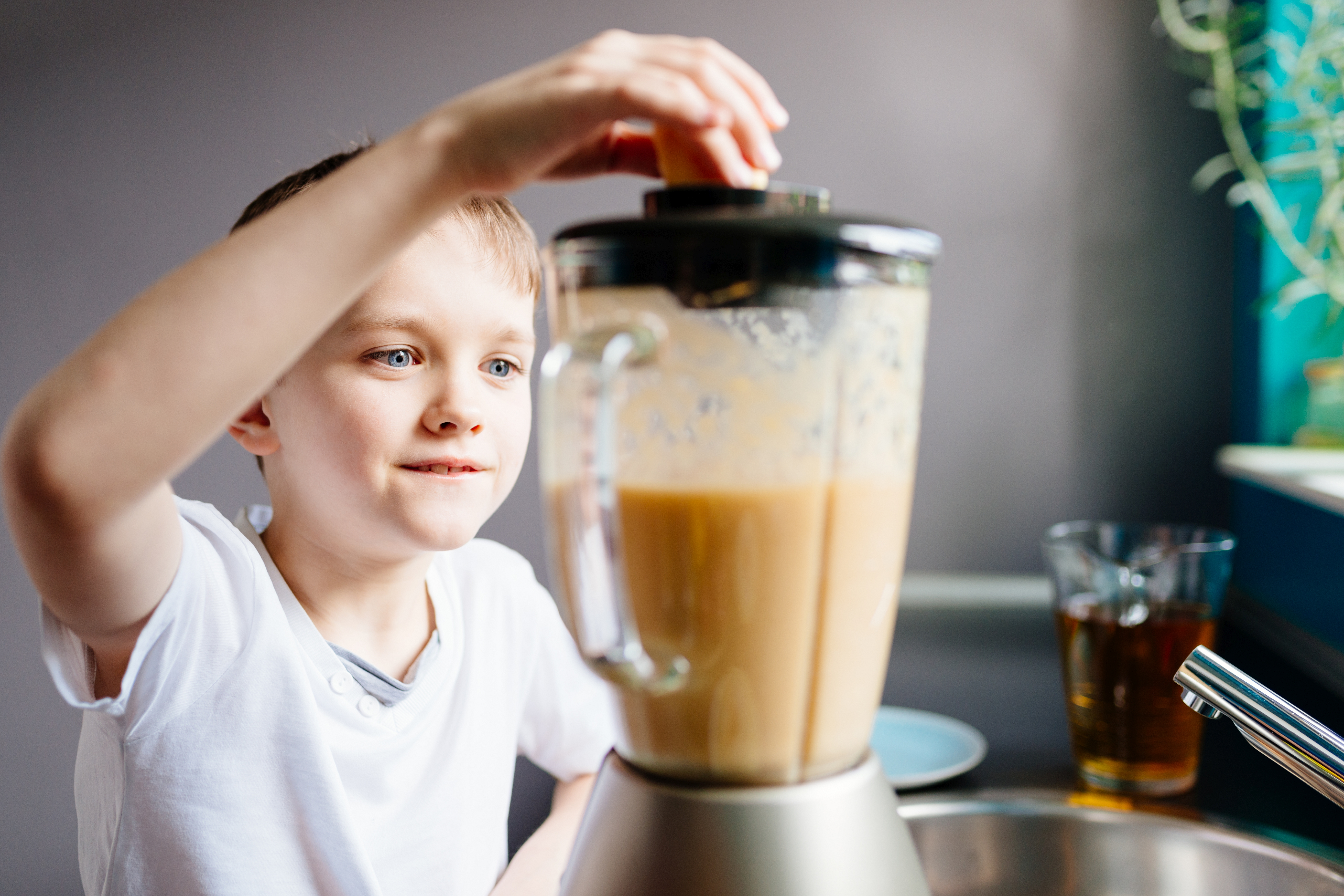 Happy little boy is making healthy fruit juice at home. Healthy eating