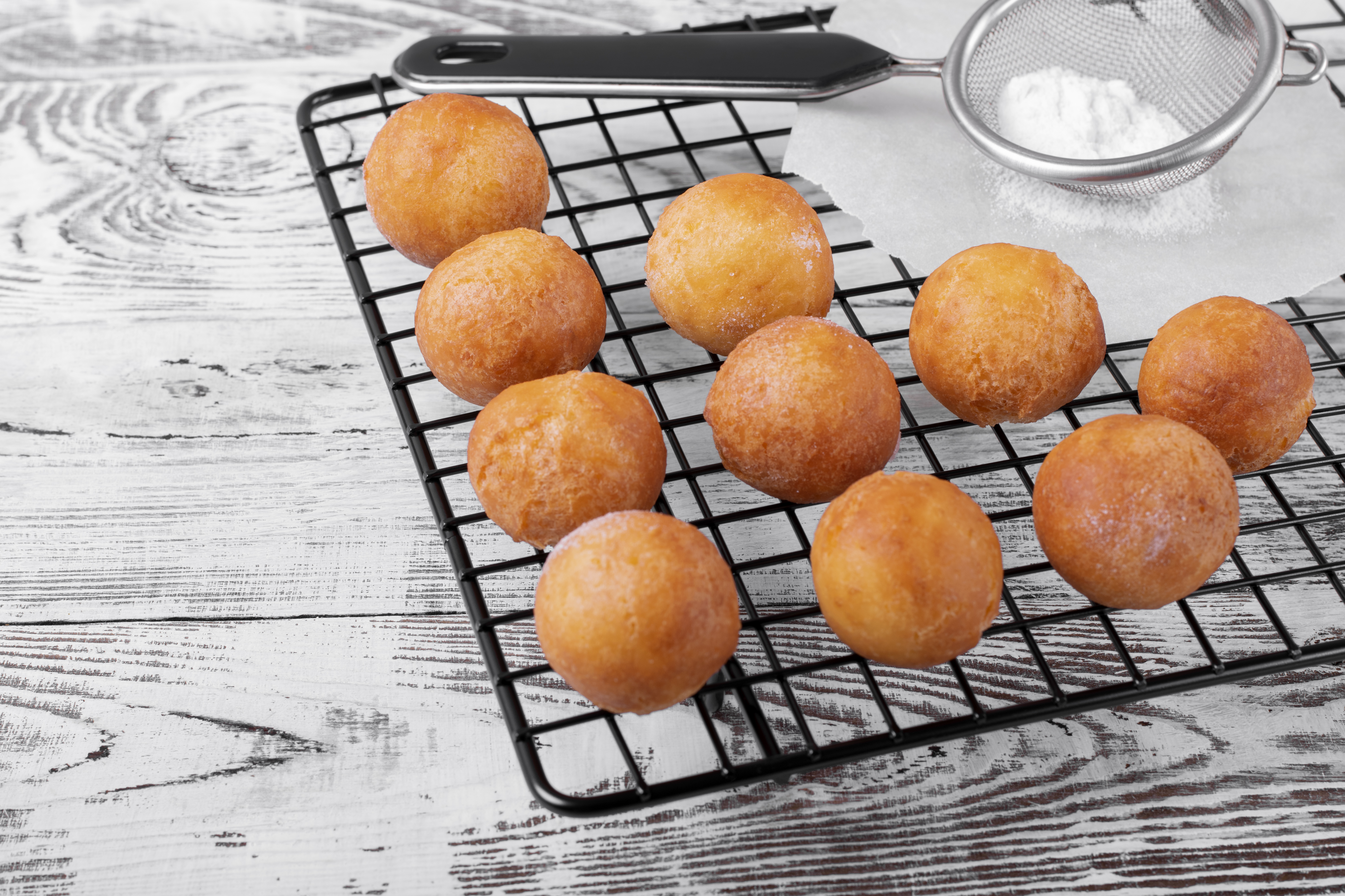 Golden round donuts on the black lattice on the white wooden table